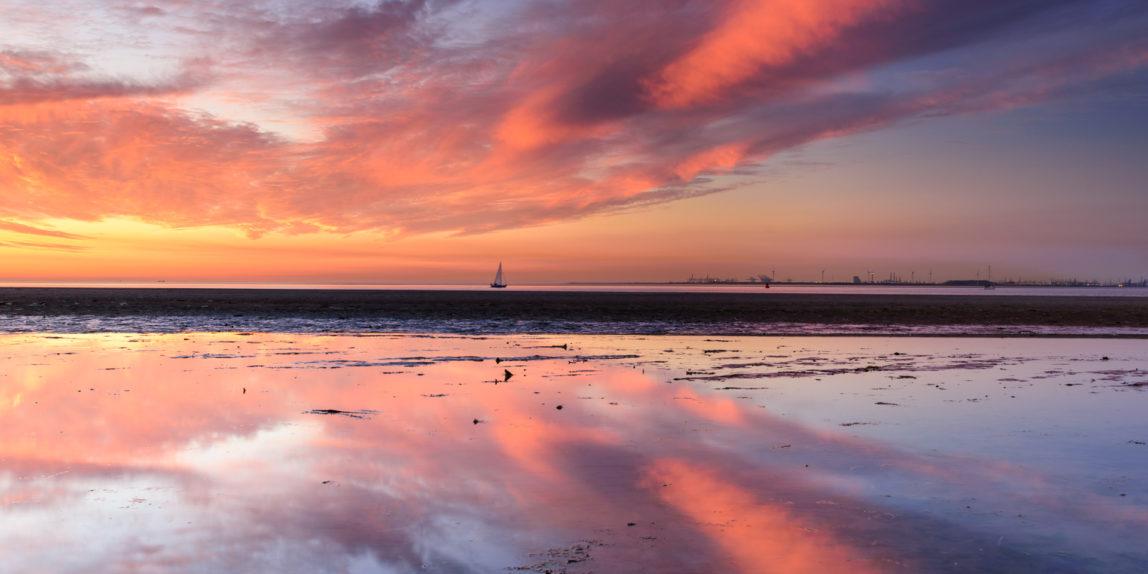 Een rood en blauw gekleurde zonsondergang gereflecteerd in het water in de Kwade Hoek.