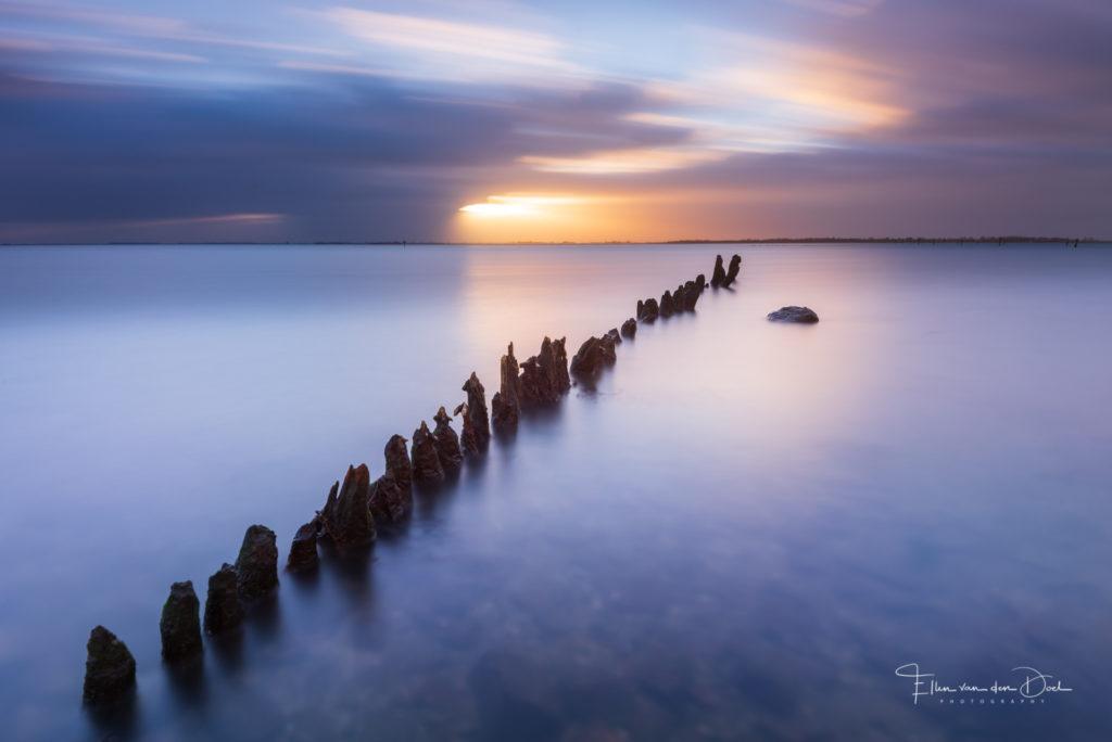 Lange sluitertijd opname van paaltjes in het water tijdens zonsondergang.