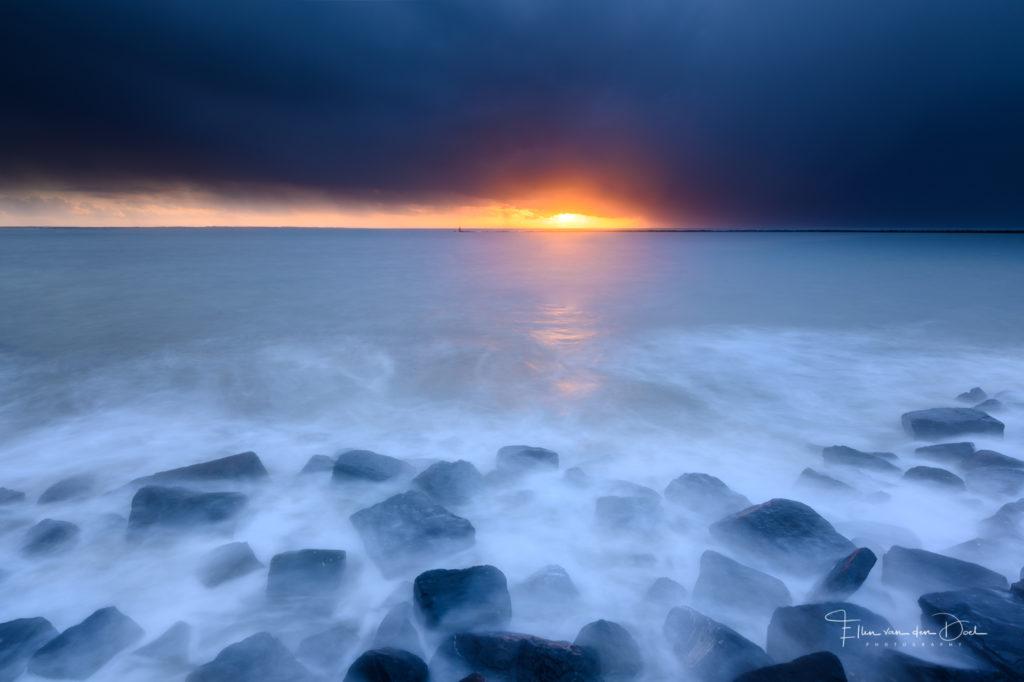 Een donkere lucht met nog net de zon eronder door boven zee