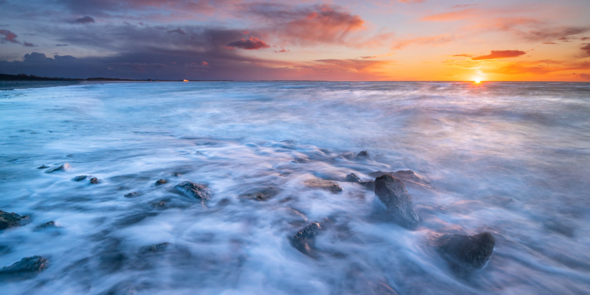 Zonsondergang aan een ruige zee