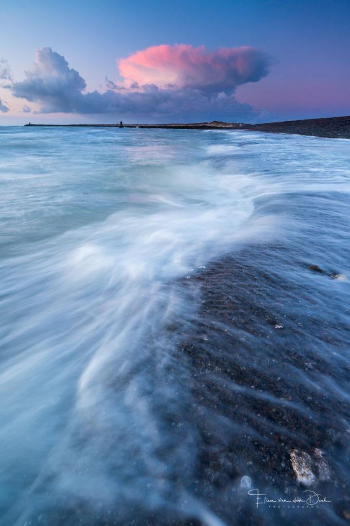 Water in beweging met aan de horizon een roze gekleurde buienlucht